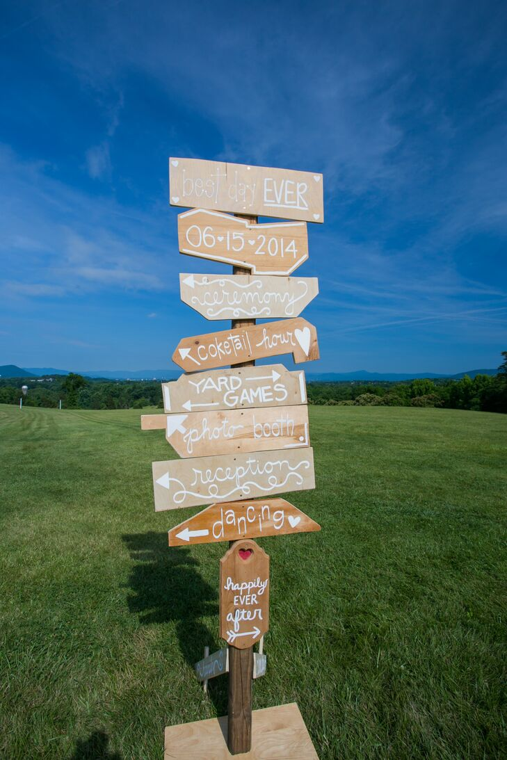 A rustic wooden sign directed guests to wedding activities.