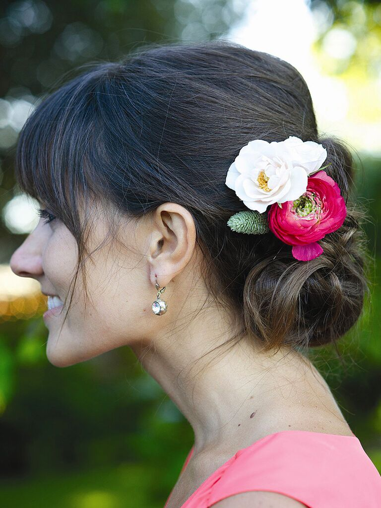Low messy bridesmaid hairstyle with fresh flowers