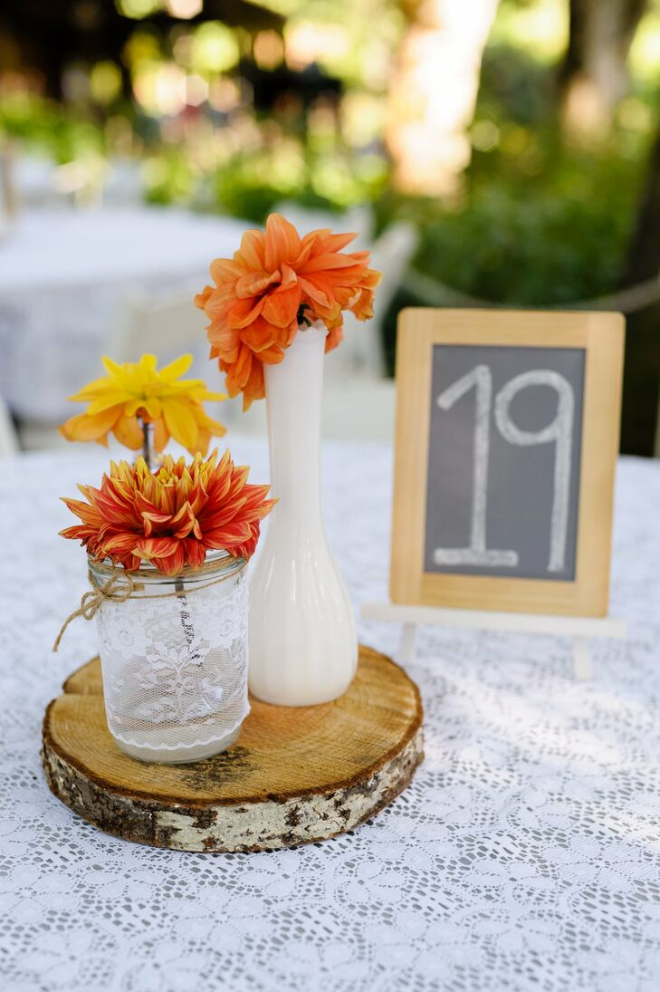 For a vintage look, the tables were covered with lace table cloths and single blooms in mismatched vases. Chalkboard table numbers and wood accents gave the tablescape a rustic edge.