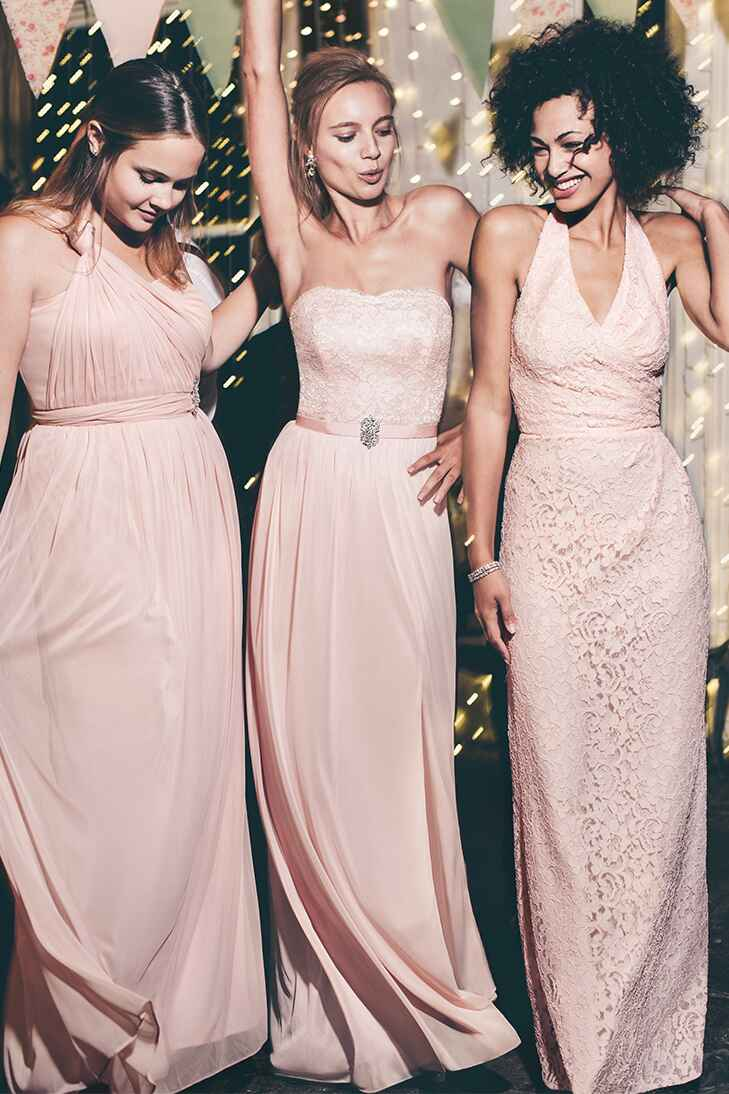 Three models in peach colored bridemaids dresses