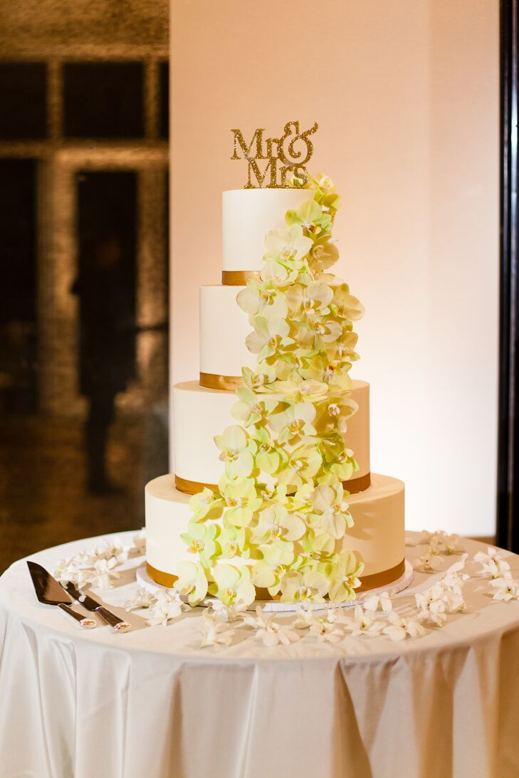 The four-tier white wedding cake had a rim of gold wrapped around the bottom of each layer, adding a touch of glam to the traditional dessert. Green orchids decorated the side of the cake, from the top all the way to the bottom.