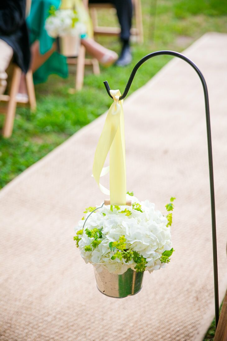 The burlap aisle was lined with shepherd's hooks that held galvanized buckets filled with hydrangeas and yellow bluporum.