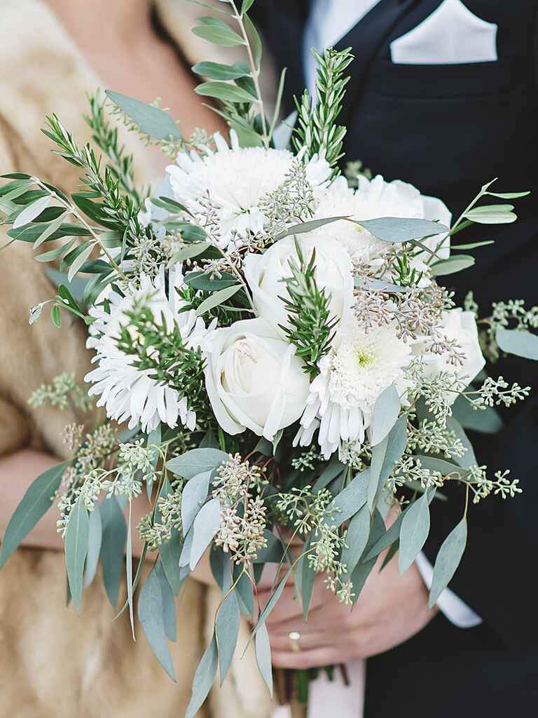 A bridal bouquet with roses and fresh herbs