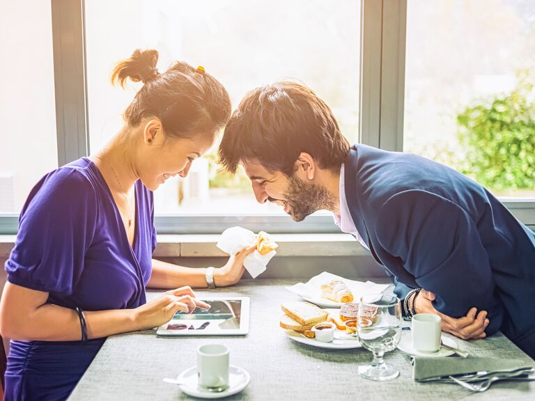 Couple eating a meal and looking over a tablet