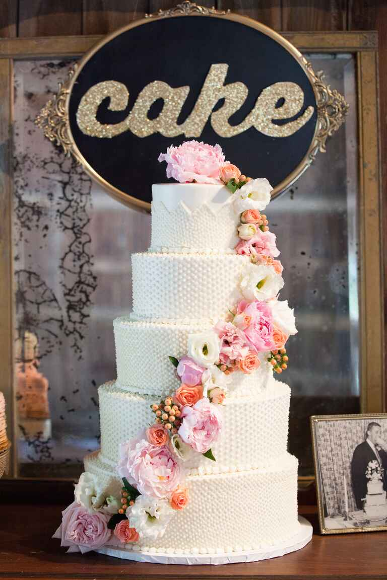 Five tiered cream wedding cake with pink and peach cascading flowers