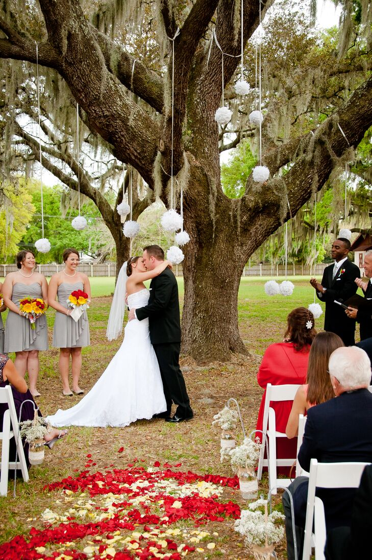 "With a grand oak tree as their backdrop and bright petals lining the aisle, Megan and Mike incorporated their third wedding color, white, with a touch of whimsy. More than a dozen ""kissing ball"" pomanders were suspended over their ceremony space as Megan and Mike shared their first kiss."