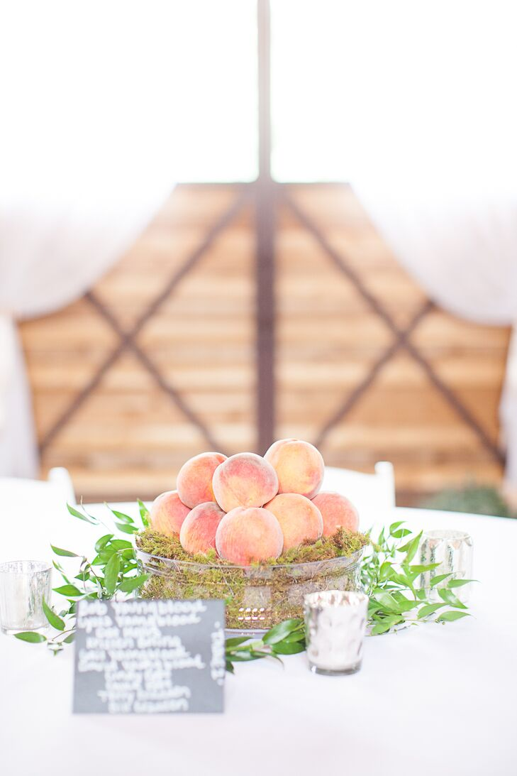 The centerpieces incorporated fresh Georgia peaches in rustic tins filled with moss and overflowing with leafy vines for a rustic, natural style.