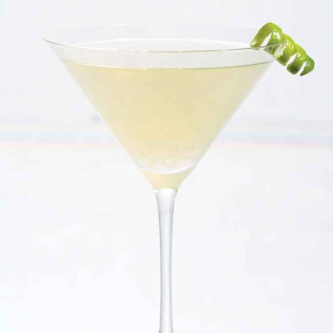 champagne colored drink in a martini glass with a lime twist