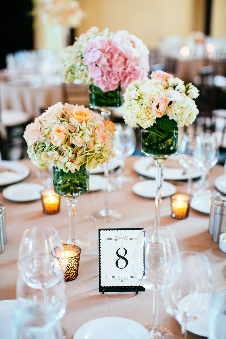 There were three versions of centerpieces at the gorgeous reception at The Liberty Hotel in Boston. The couple wanted the decorations to add variety and depth to the room. One version included pink, ivory and green hydrangeas and roses in varying height glass vases.