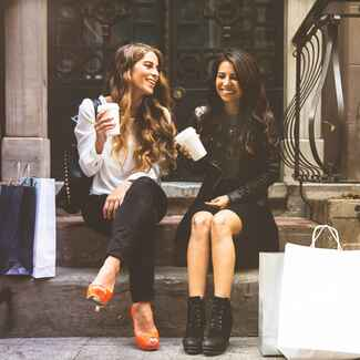 Two friends on an apartment stoop with shopping bags and coffee