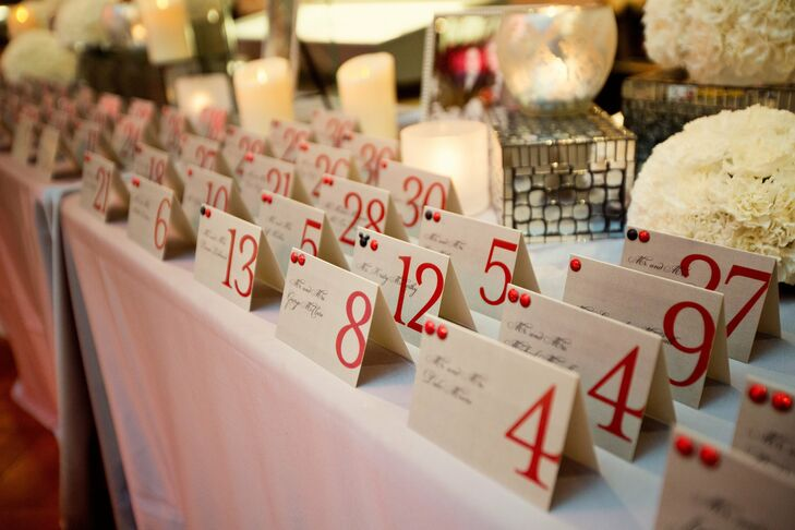 The tented escort cards were printed on chrome stationery with an oversized red number. Ten white flower balls in different sizes displayed at different heights decorated the table along with candles at varying levels.