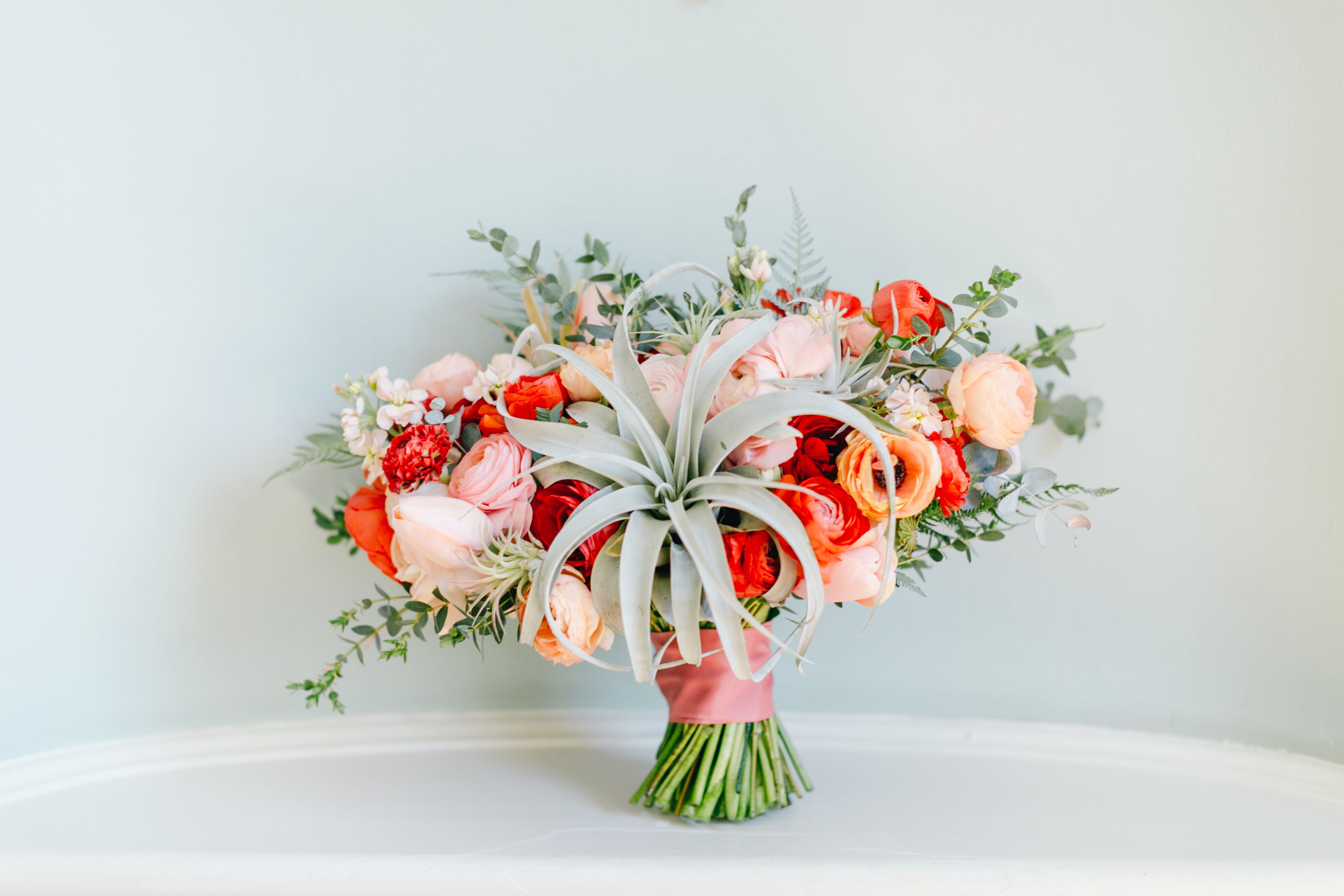 Red And Blush Bouquet With Ranunculuses And A Statement Air Plant