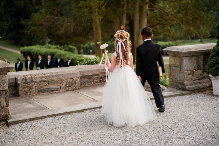 The flower girl wore a white tulle dress and a pink rose flower crown in her hair. She was accompanied by the ring bearer, who wore a classic black tuxedo.
