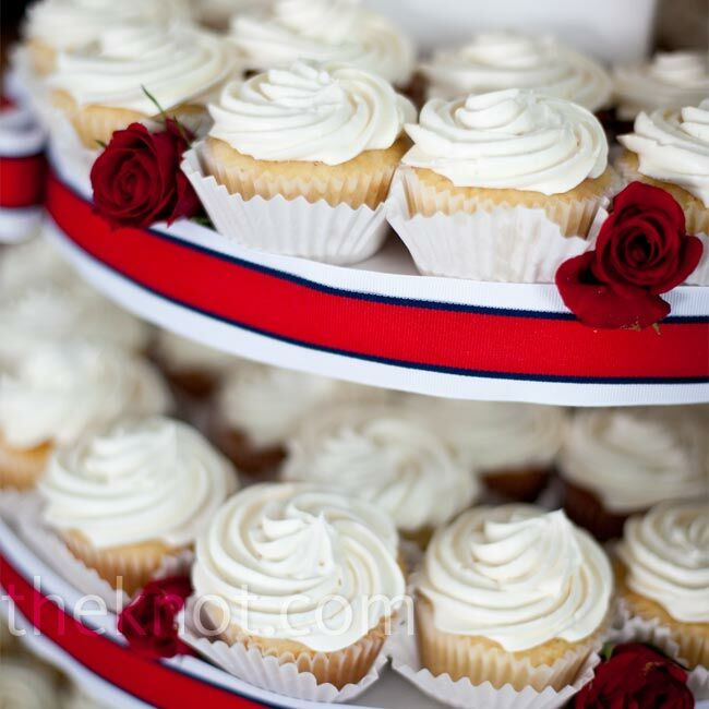 A red, white, and blue tower displayed delicious cupcakes iced in white buttercream. Red rose petal and ribbon details mimicked the bouquets.