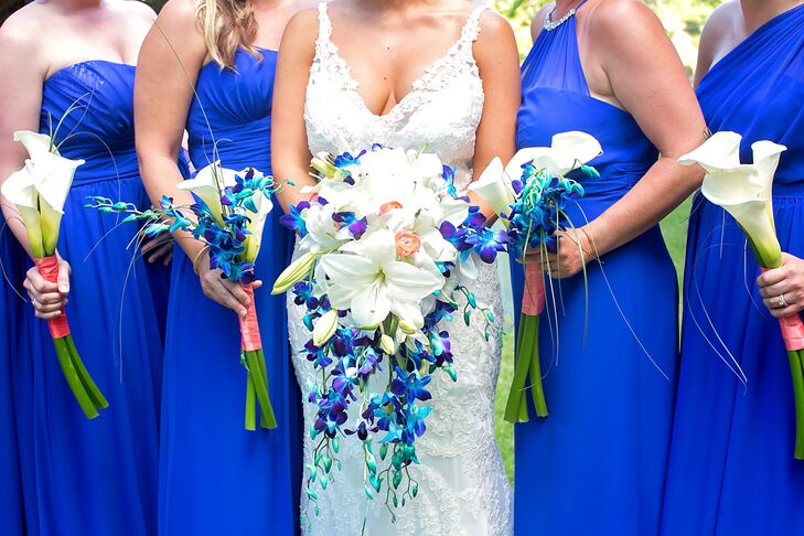Ashley knew she wanted a cascading bouquet that mirrored the look of stargazer lilies. With some help from the pros at Atmospheres Floral and Decor, she carried just that. Her lush arrangement overflowed with white asiatic lilies, coral ranunculus and bright blue orchids. Her bridesmaids held similar looks with white white calla lilies and blue orchids inside a coral wrap.