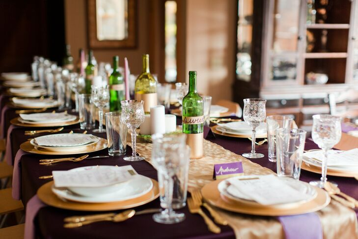 The elegant table decor had deep purple tablecloths, gold dishware and empty wine bottles and candles as centerpieces.