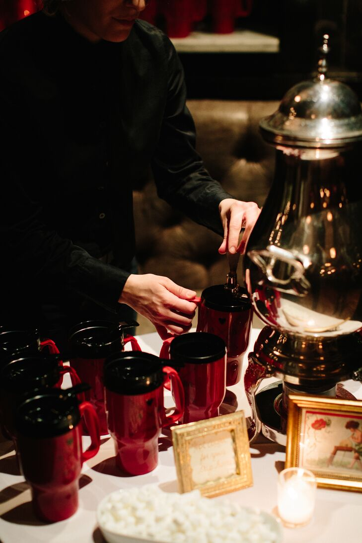 "To send guests off at the end of the night, a hot cocoa station was set up with steaming hot chocolate, homemade marshmallows and the couple's red mug favors. ""We wanted wedding favors that would be useful beyond just our wedding day,"" Allison says."