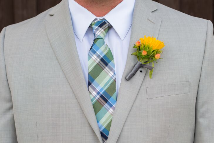 The groom wore a sunflower and hypericum berry boutonniere on his lapel.