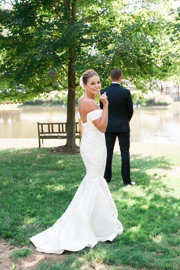 "Drawing inspiration from the wedding's fusion of laid-back and elegant styles, Rebecca opted for a simple, chic Kelly Faetanini gown. The silk chiffon dress featured a mermaid-style silhouette with a low-cut back and off-the-shoulder neckline, as well as fabric-covered buttons running down the back. ""Words can hardly describe the feeling as I walked down the aisle toward the man of my dreams with my dad by my side, veil blowing in the breeze and the sun shinning through the trees behind us, all in my backyard. It was simply magical,"" Rebecca says."