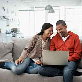 Couple sitting on the couch and looking at a laptop