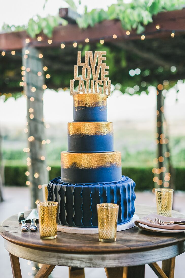 "In a nod to the couple's theme, a gold ""live, love, laugh"" topper and gilded brush strokes adorned the navy wedding cake."