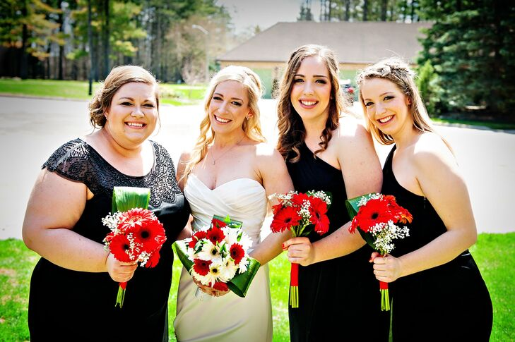 The bridesmaids wore black dresses and carried red gerbera daisy bouquets.