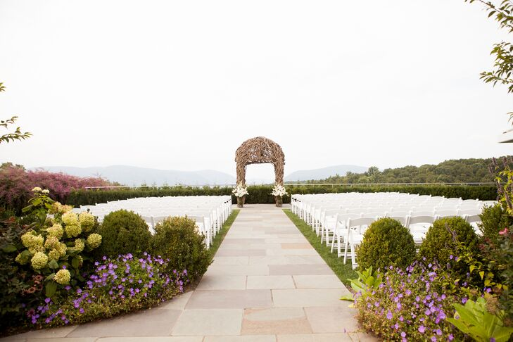 """While we were looking at venues, I knew I wanted to get married outside,"" Kelley says. ""Once I saw the ceremony garden at the Garrison, I knew this was going to be the place we say 'I do.' It has a mix of country and elegance, which was exactly what I wanted."" With this in mind, they focused on minimal added decor—except this incredible wooden arbor! About 180 chairs led the way to their ceremony space, while greenery, natural green hydrangeas and little purple flowers marked the entrance."