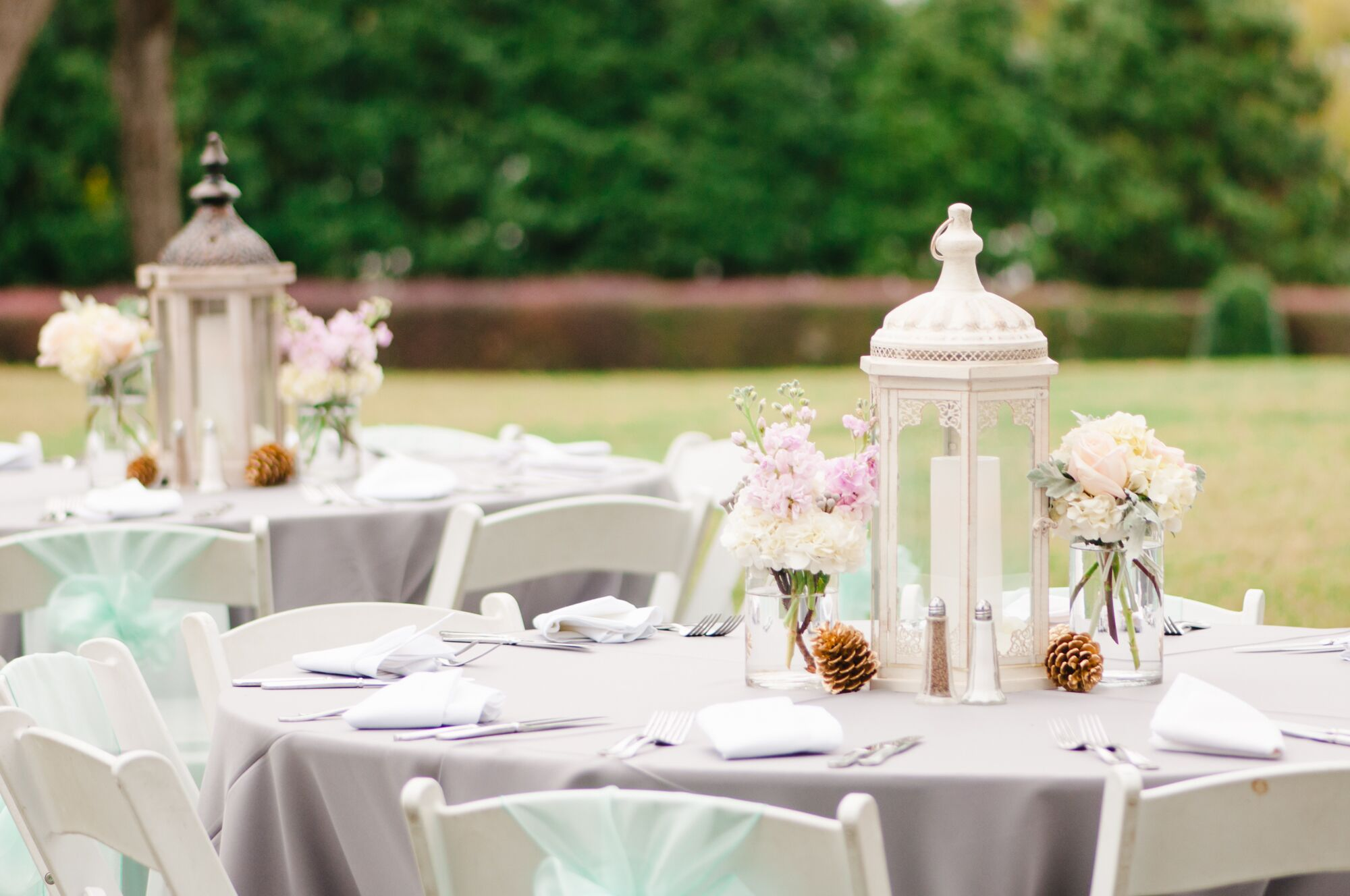 White lantern centerpieces with pastel flowers