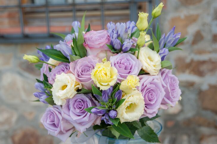 The bridal bouquet was an arrangement of purple, ivory and yellow roses with green accents, designed by Funkybird Wedding Design.