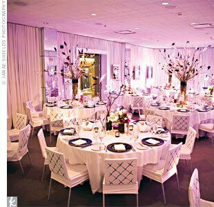 Purple lighting cast a hip yet romantic glow around the cylindrical vases, which were filled with curly willow and decorated with black ostrich feathers, candles and crystals.