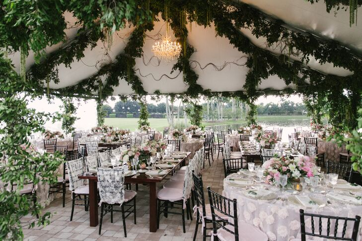 """One thing to note about our reception was that everything was created from scratch,"" says Joyce. Her and Jay designed the tented reception two months before their wedding. It was decorated with chandelier lighting, mixed vintage silver chargers, grape vine and eucalyptus garlands, romantic floral centerpieces and dark chiavari chairs."
