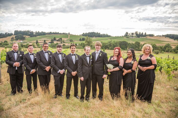 Gary and Paul stood in line with their wedding party matching in black. The groomsmen wore black tuxedos that differed slightly from Gary's and Paul's look, while the women wore floor-length elegant black dresses.