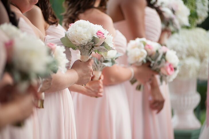 Nicole's bridesmaids carried bouquets with white peonies, pink roses and dusty miller with their blush dresses.