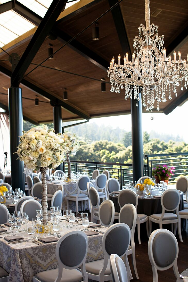 Chandeliers hung over elegantly decorated tables. Gray linens and modern white chairs were accented with varying centerpieces of white and yellow flowers.