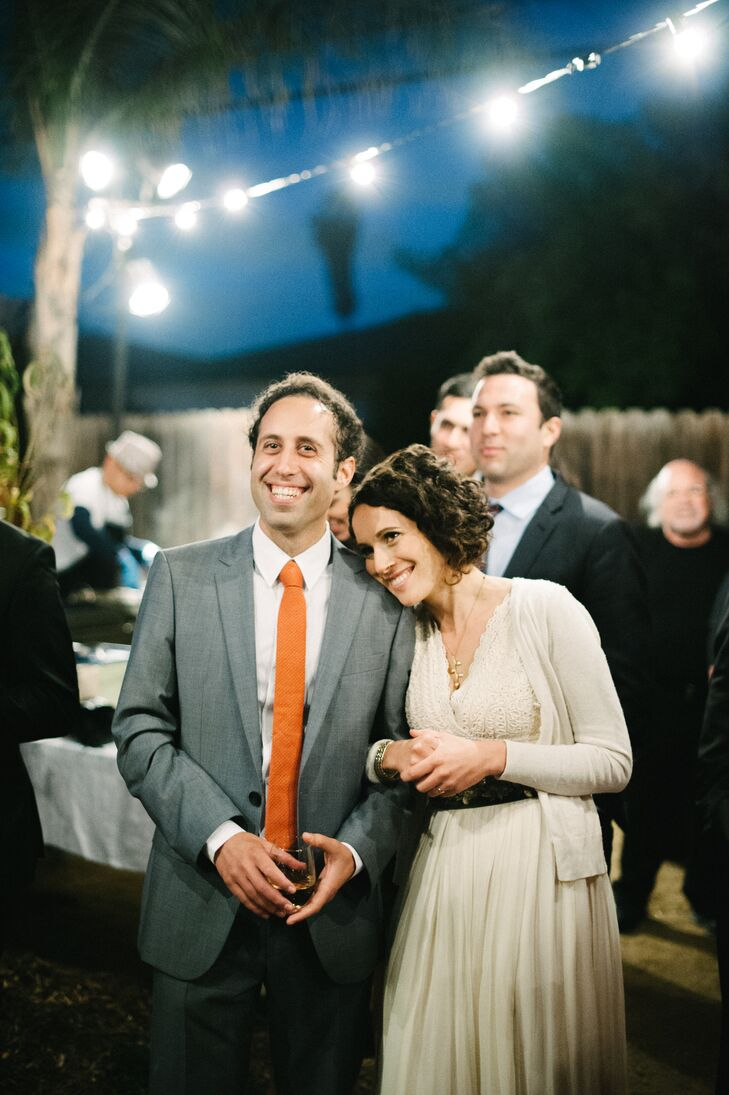 The newly married couple leaned on one another underneath twinkling lights during the backyard reception. Chris changed his tie from black to orange for the reception, and Emily put on a cardigan over her ivory wedding dress.