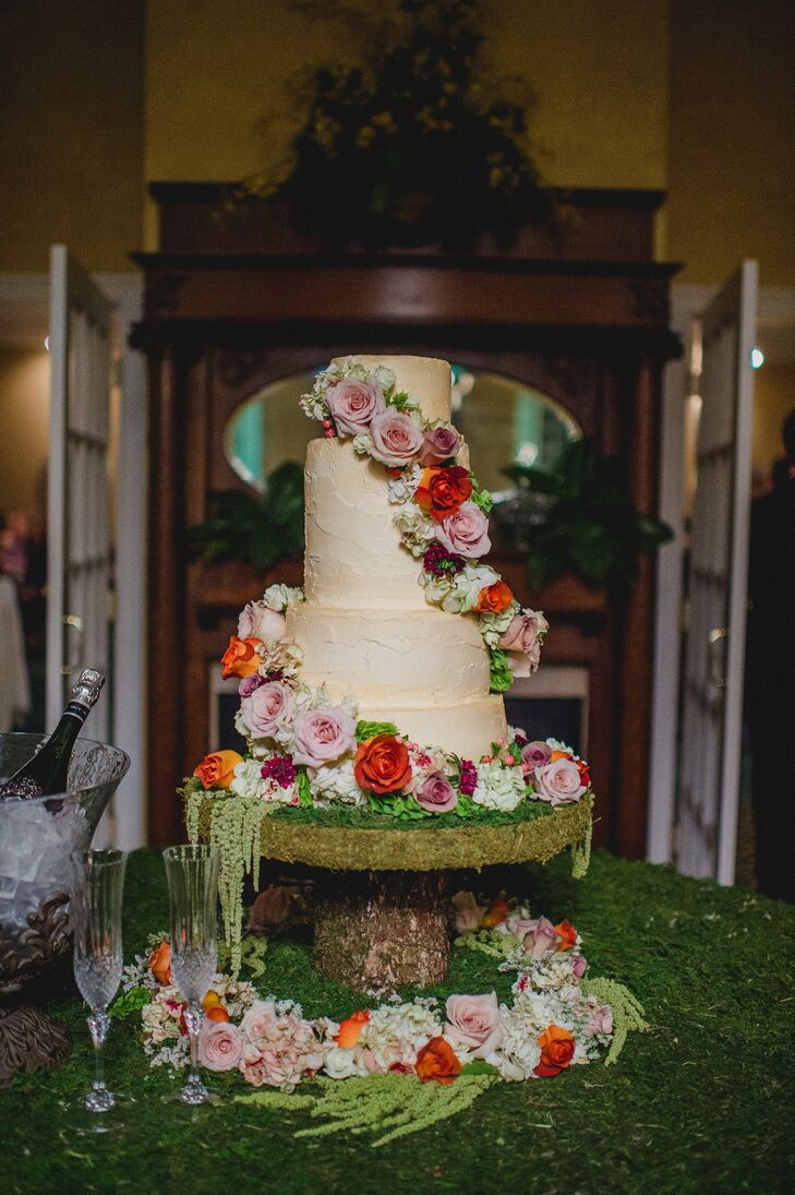 Their cake was nothing short of incredible and truly captured the woodland idea with a custom moss-covered stand. Under the four-tier buttercream cake, greenery even covered the table. Plus, a garland of red, mauve and orange roses, as well as white hydrangeas, red hypericum berries and burgundy delphiniums draped over every tier. For guests who wanted something different, Brooklee and Charley also had a sundae bar on the original ice cream cart from his grandfather's company, Redbird Ice Cream.