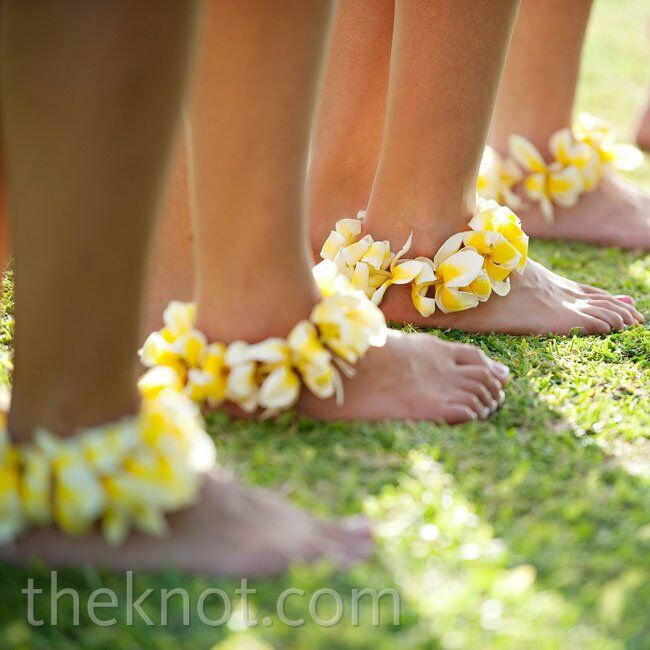 The bridesmaids wore yellow plumeria around their ankles and went barefoot for a natural, laid-back look.