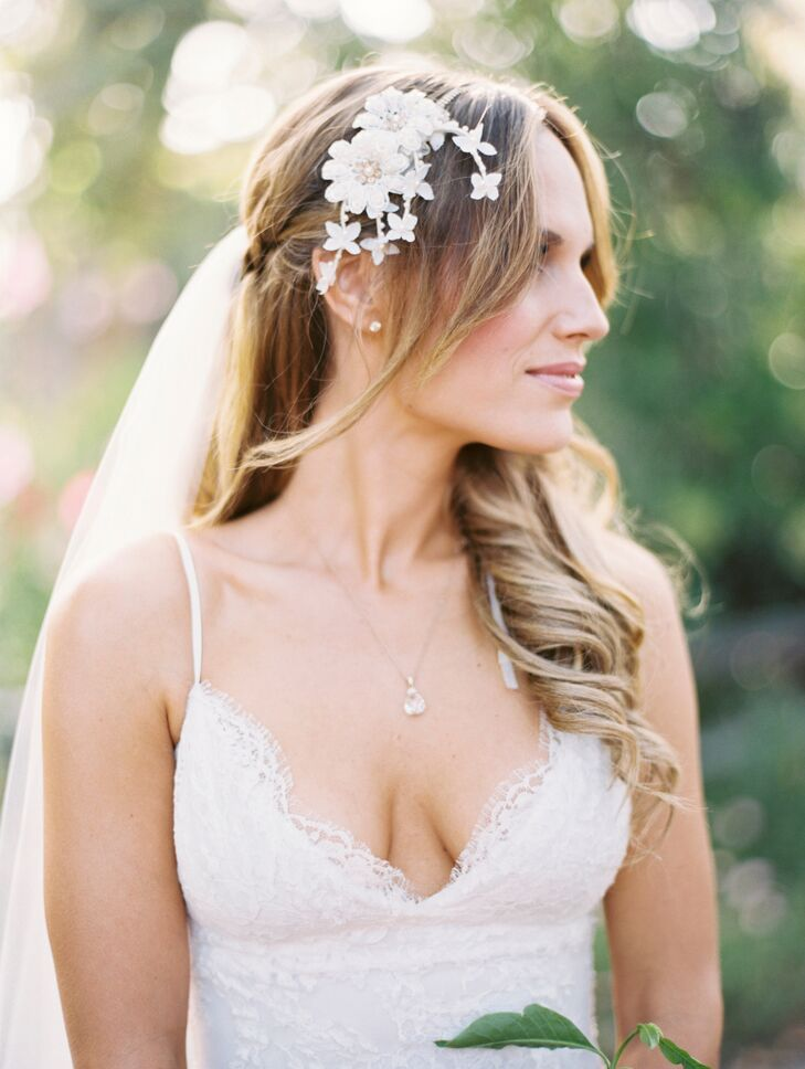 Stacy wore her hair down in curls to go with her romantic look, pinned with a white flower clip on the right side. At first, she wasn't going to invest in a veil to wear on the day of the wedding. But two weeks before the wedding, she changed her mind and rush-ordered a beautiful medium-length veil made of tulle.