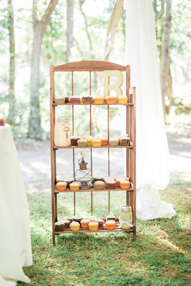 Instead of a traditional dessert table, Tangie and Mike set up this wooden bookshelf for their cupcakes. Little vintage-style trinkets, such as glass lanterns and mason jars, brought the country wedding theme to life.