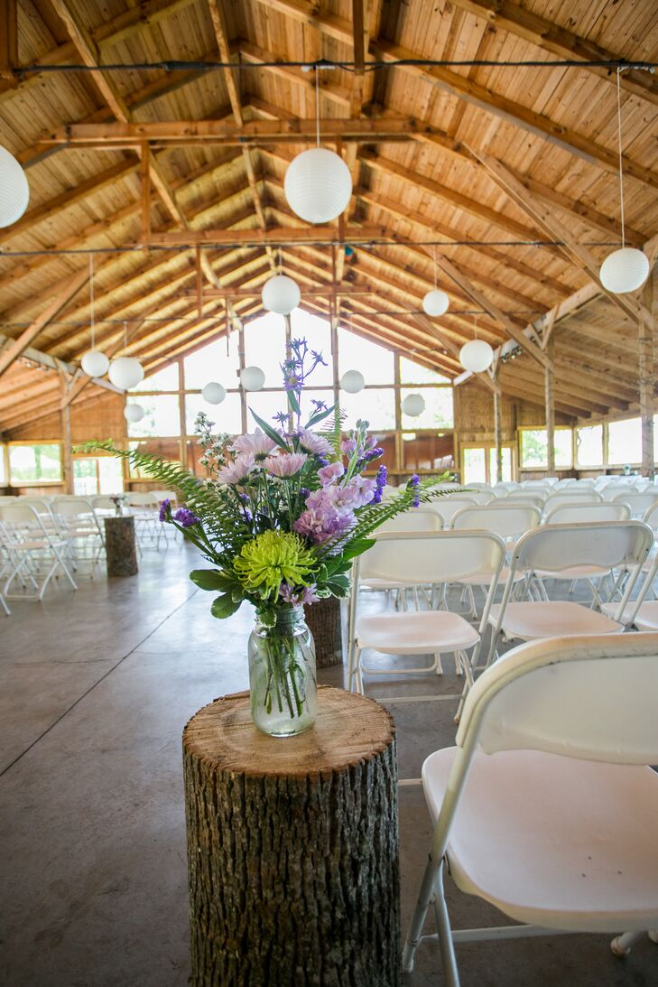 Tree stumps line the ceremony aisle with large wildflower bouquets.