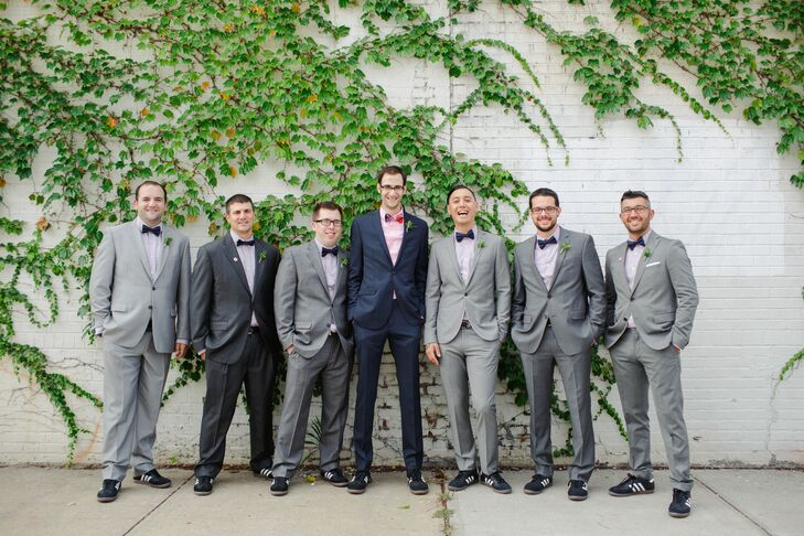 "To make things easy for his groomsmen, Michael encouraged the guys to wear gray suits they already owned and supplied them with matching white shirts and dark blue bow ties from Express. For his own look, Michael sported a blue Ben Sherman suit, pink shirt and a multicolored plaid bow tie. To tie their looks together, one of Michael's groomsmen gave everyone pizza-slice socks to wear with their Adidas Samba shoes. ""Chris bought them as a surprise for Risa,"" Michael says, ""since she loves pizza."""