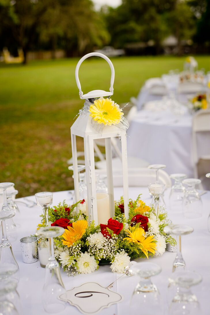 Megan and Mike decorated their outdoor reception with a vintage touch. Every white-linen-covered  table, including the sweetheart table, had a different lantern centerpiece. To incorporate their wedding colors with a natural touch, halos of red roses, baby's breath, white chrysanthemums and yellow daisies surrounded each accent.