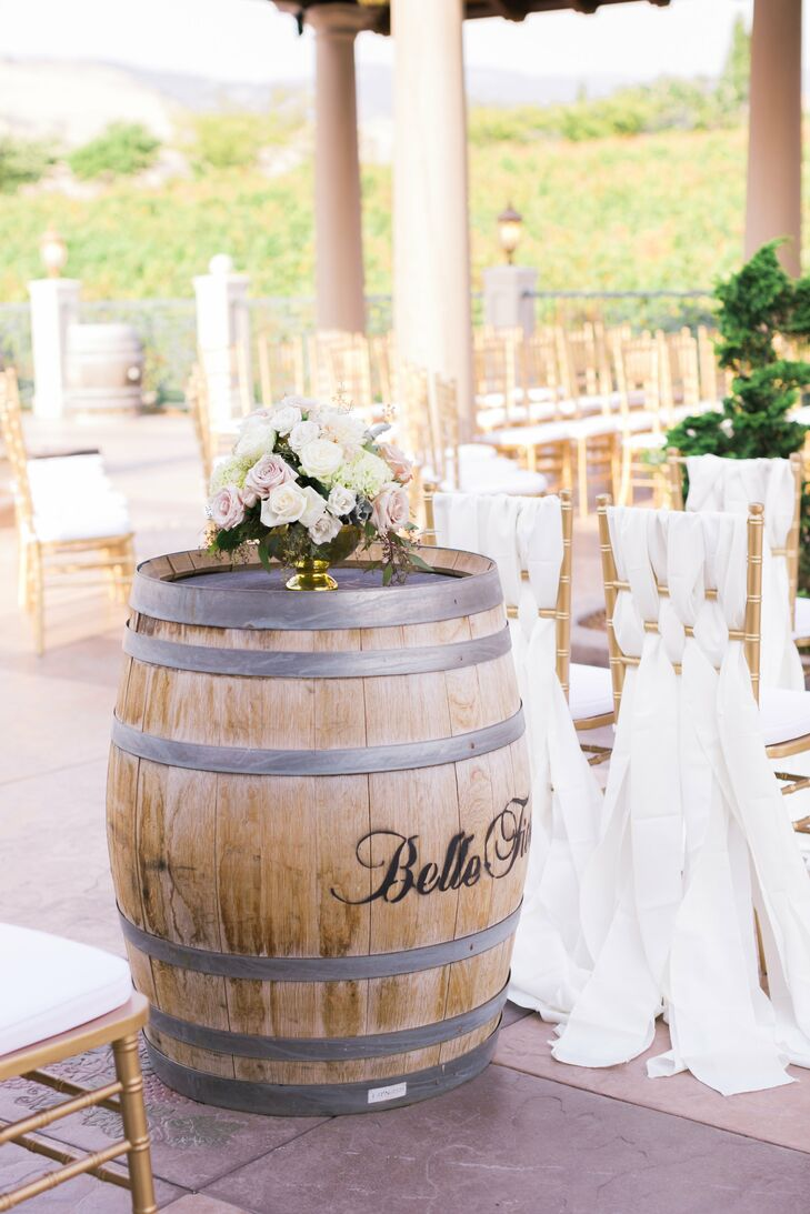 At the ceremony site, wine barrels displayed lush floral arrangements, and ornate gold chairs were draped with soft satin.
