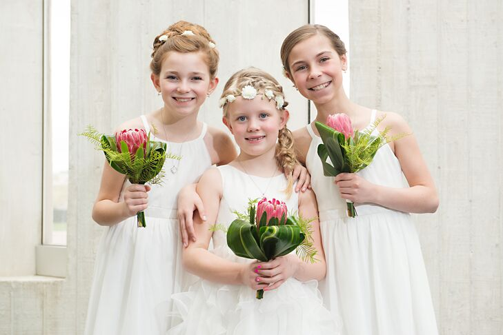 The mothers of the flower girls had free rein in choosing their daughters' dresses. The flower girls carried one protea flower that matched flowers in Ann's bouquet.