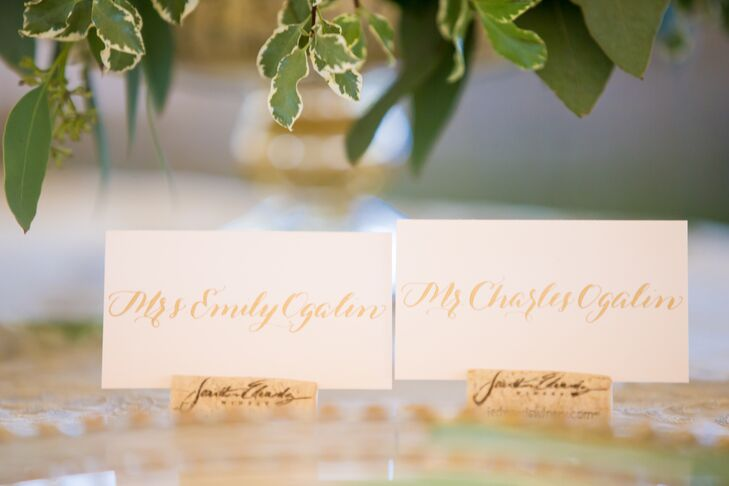 Guests found their escort cards at a wine-barrel table that held wine bottles with labels for each table's seating arrangement. Marcardin Calligraphy inscribed guests' names in gold ink onto delicate blush paper in Jonathan Edwards corks, which the couple collected throughout the year leading up to their wedding.