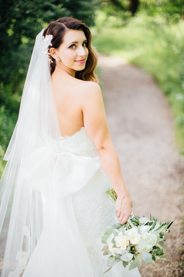 Lauren's delicate cathedral-length French lace veil was made by designer Judd Waddell. Cascading loose curls were swept to the side for a pretty, romantic look.