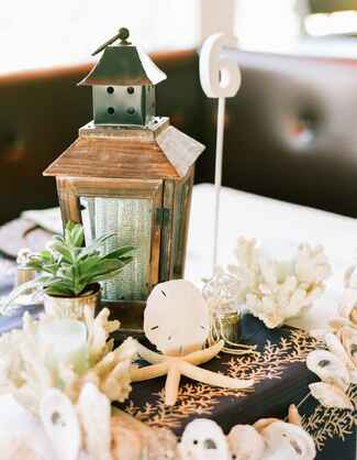 Coral and seashell beach-inspired wedding reception centerpiece