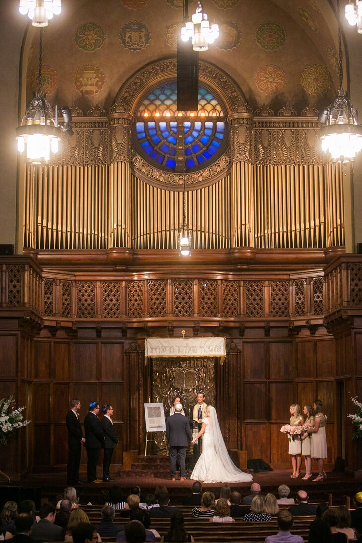 "Ashley and Adam had their Jewish ceremony at Temple Beth Israel in Portland, Oregon, which had an ornate interior that required little extra decorating. ""We had our wedding ceremony at Temple Beth Israel in Portland near downtown,"" Ashley says. ""Having the ceremony here was really important to us on a personal level, since we had been attending this synagogue together while dating. We fell in love both with the congregation and the stunning architectural beauty of the building."""