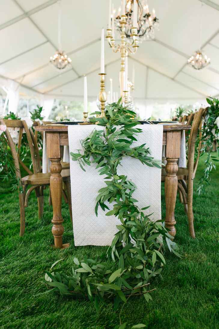 Tented outdoor wedding reception with white table runners and garland
