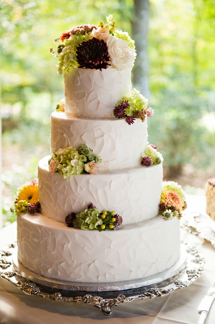 Annslee and Alex had a traditional white buttercream wedding cake that had scattered fall-color flowers around the four textured tiers. The cake matched the laid-back environment with a hint of classic.